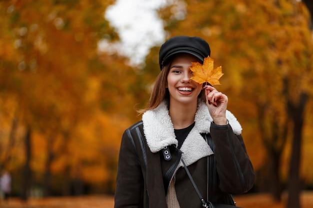 Dość pozytywna młoda kobieta w modnym czarnym kapeluszu w stylowej brązowej kurtce trzyma żółto-pomarańczowy liść klonu w pobliżu twarzy i uśmiecha się w parku. zabawna dziewczyna cieszy się weekendem w jesiennym lesie.