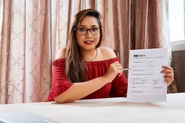 Dość pozytywny młody menedżer nieruchomości wyjaśniający, jak wypełnić dokument informacjami bankowymi