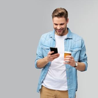 Dość przypadkowy mężczyzna w koszuli dżinsy trzymając telefon i filiżankę kawy na wynos