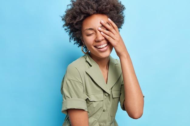 Dość radosna afro amerykanka trzyma dłoń na twarzy, bardzo się cieszy, zamyka oczy, uśmiecha się szeroko, nosi stylową sukienkę odizolowaną na niebieskiej ścianie