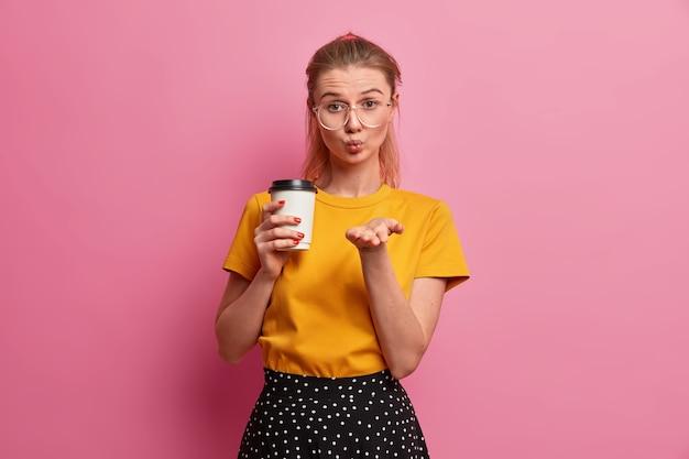 Dość romantyczna dziewczyna wysyła tylko miłość, ma zaokrąglone usta, wysyła mwah, trzyma kawę na wynos, ubrana swobodnie