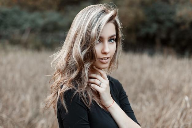 Dość śliczna młoda kobieta z naturalnym makijażem o niebieskich oczach i cudownym uśmiechu w czarnej modnej koszulce na polu wśród suchej trawy