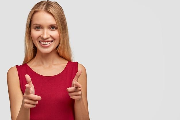 Dość słodka młoda kobieta o radosnym wyrazie twarzy, wskazuje na ciebie lub strzela z pistoletu palcami, nosi czerwoną kamizelkę