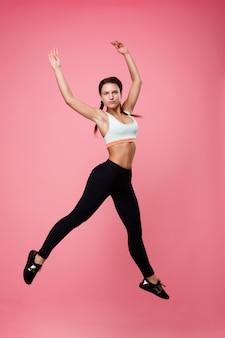 Dość sportowa kobieta w topie i leginsach skacząca jak baletnica