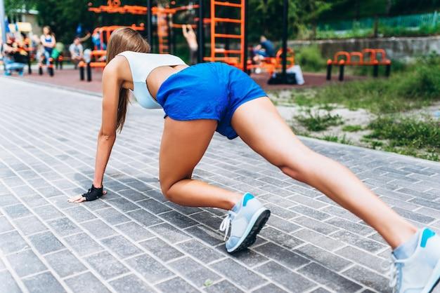 Dość sportowy biegacz dziewczyna na punkcie startowym przygotowującym się do biegu na świeżym powietrzu na ulicy