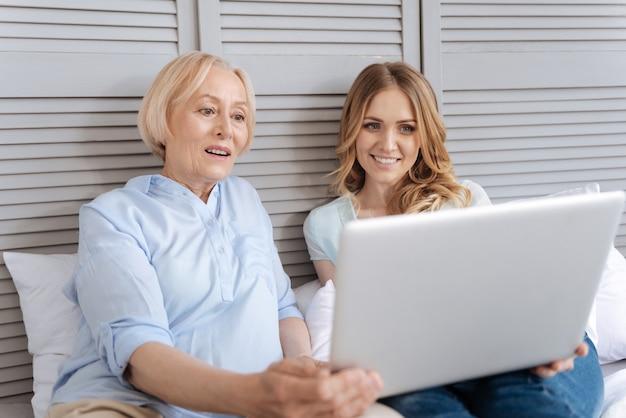 Dość starsza kobieta i jej jasnowłosa dorosła córka oglądają wideo na laptopie, podczas gdy matka patrzy na ekran ze zdziwieniem