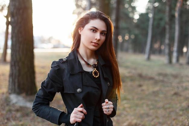 Dość stylowa kobieta w czarnym płaszczu spaceru w parku