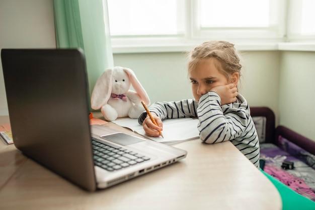 Dość stylowa uczennica ucząca się matematyki podczas lekcji online w domu, samoizolacja