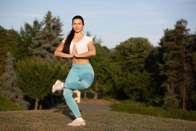 Dość szczupła dziewczyna robi ćwiczenia jogi na tle lasu. miejsce na tekst