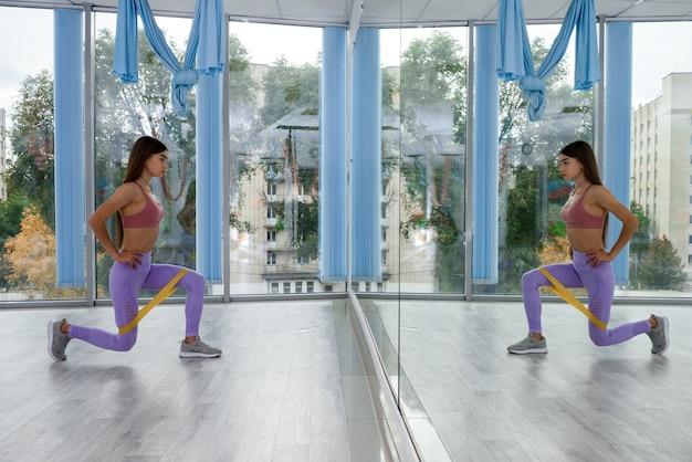 Dość szczupła dziewczyna sportowy strój do ćwiczeń rozciągających nogi lub ręce z gumą sportową. kobieta actime robi treningu w studio fitness