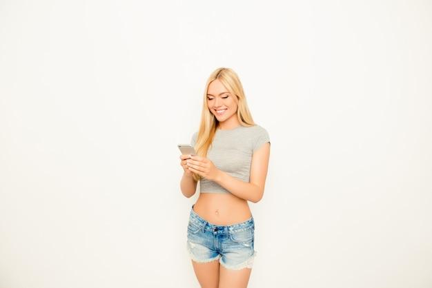 Dość szczupła dziewczyna wpisując sms na telefon komórkowy