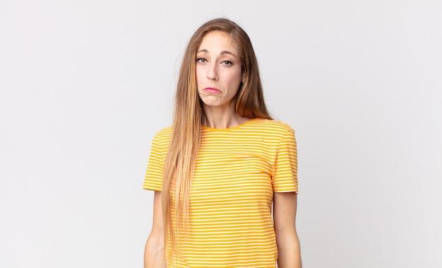 Dość szczupła kobieta czuje się smutna i marudna z nieszczęśliwym spojrzeniem, płacze z negatywnym i sfrustrowanym nastawieniem