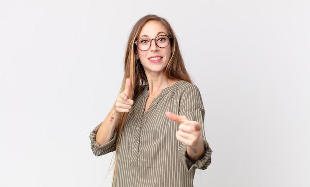 Dość szczupła kobieta czuje się szczęśliwa, fajna, usatysfakcjonowana, zrelaksowana i odnosząca sukcesy, wskazując na aparat, wybierając ciebie
