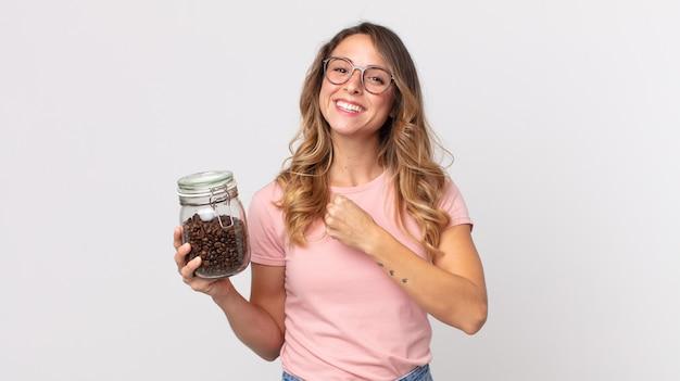 Dość szczupła kobieta czuje się szczęśliwa i staje przed wyzwaniem lub świętuje i trzyma butelkę ziaren kawy