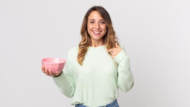 Dość szczupła kobieta czuje się szczęśliwa i wskazuje na siebie z podekscytowaną i trzymającą pustą miskę garnka