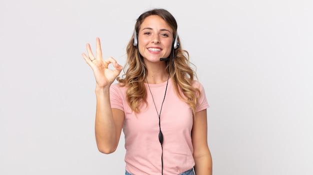 Dość szczupła kobieta czuje się szczęśliwa, pokazując aprobatę dobrym gestem. asystent operatora ze słuchawkami
