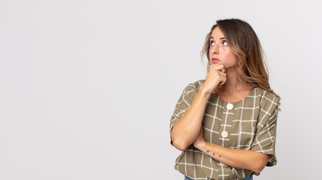 Dość szczupła kobieta czuje się zamyślona, zastanawia się lub wyobraża sobie pomysły, marzy i patrzy na kopiowanie przestrzeni