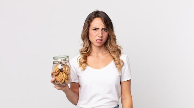 Dość szczupła kobieta czuje się zdezorientowana i zdezorientowana, trzymając szklaną butelkę po ciastkach