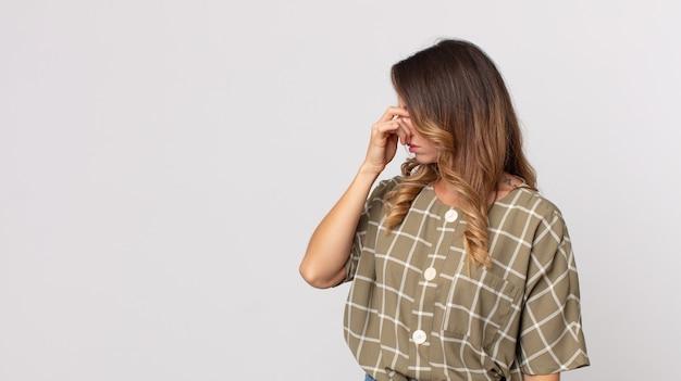 Dość szczupła kobieta czuje się zestresowana, nieszczęśliwa i sfrustrowana, dotyka czoła i cierpi na migrenę lub silny ból głowy