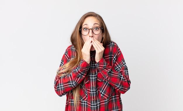 Dość szczupła kobieta czuje się zmartwiona, zdenerwowana i przestraszona, zakrywa usta rękami, wygląda na zaniepokojoną i pomieszała się