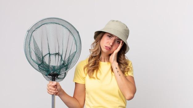 Dość szczupła kobieta czuje się znudzona, sfrustrowana i senna po męczącym kapeluszu i trzymaniu sieci na ryby