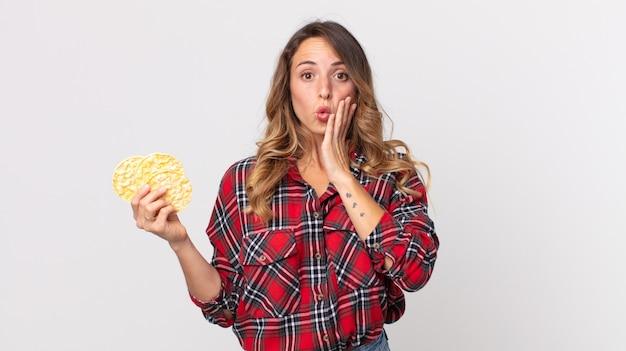 Dość szczupła kobieta czuje się zszokowana i przestraszona i trzyma dietetyczne ciastka ryżowe