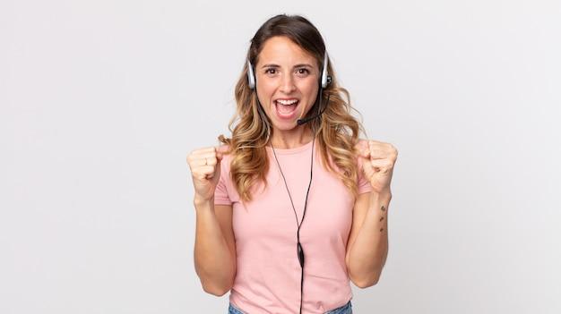 Dość szczupła kobieta czuje się zszokowana, śmieje się i świętuje sukces. asystent operatora z zestawem słuchawkowym