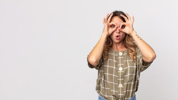 Dość szczupła kobieta czuje się zszokowana, zdumiona i zaskoczona, trzymająca okulary ze zdumionym, niedowierzającym spojrzeniem