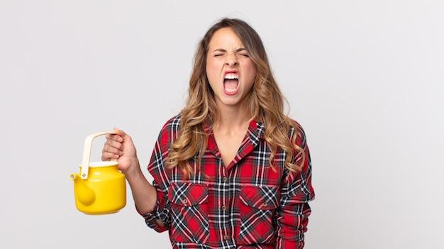 Dość szczupła kobieta krzycząca agresywnie, wyglądająca na bardzo rozgniewaną i trzymająca czajnik