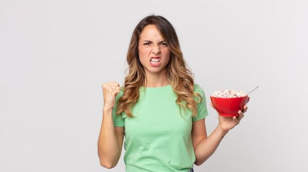 Dość szczupła kobieta krzycząca agresywnie z gniewnym wyrazem twarzy i trzymająca miskę śniadaniową