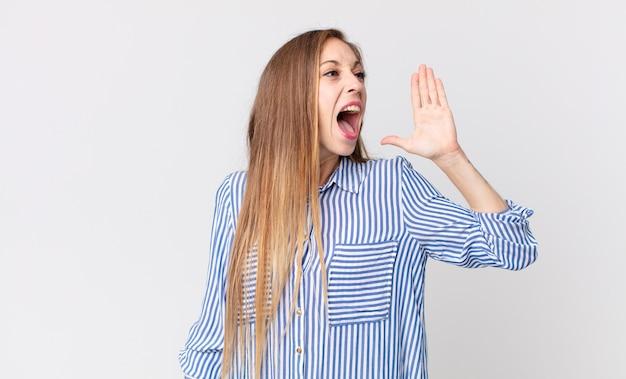 Dość szczupła kobieta krzyczy głośno i ze złością, żeby skopiować miejsce z boku, z ręką przy ustach