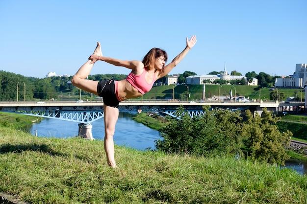 Dość szczupła kobieta praktykuje jogę na świeżym powietrzu