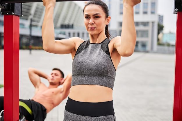 Dość szczupła kobieta robi podciąganie na drążku, podczas gdy muskularny mężczyzna robi brzuszki brzucha na boisku