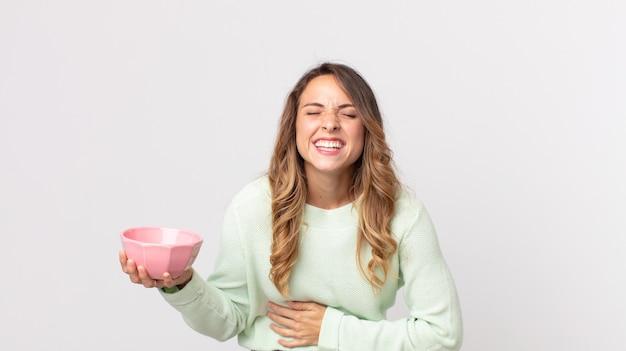 Dość szczupła kobieta śmiejąca się głośno z jakiegoś zabawnego żartu i trzymająca pustą miskę garnka