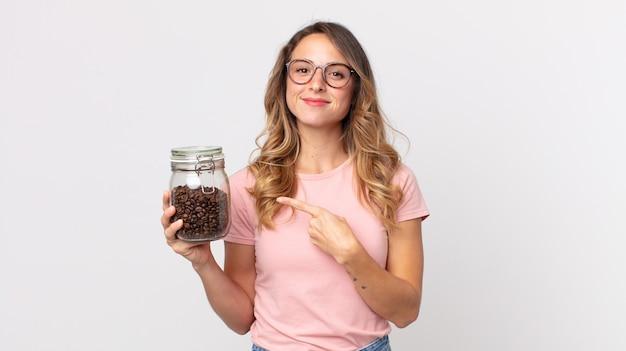 Dość szczupła kobieta uśmiecha się radośnie, czuje się szczęśliwa i wskazuje na bok i trzyma butelkę ziaren kawy