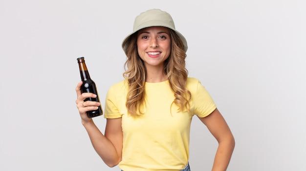 Dość szczupła kobieta uśmiechając się szczęśliwie z ręką na biodrze i pewnie i trzymając piwo. koncepcja lato