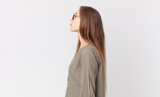 Dość szczupła kobieta w widoku profilu, chcąca skopiować przestrzeń do przodu, myśląca, wyobrażająca sobie lub marząca