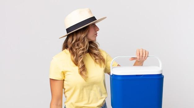 Dość szczupła kobieta w widoku profilu myśli, wyobraża sobie lub marzy i trzyma letnią lodówkę piknikową