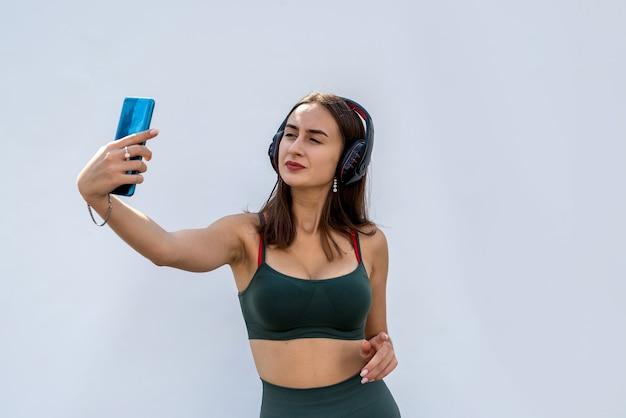 Dość szczupła kobieta w zielonym stroju sportowym i słuchawkach trzymająca telefon słucha muzyki po treningu
