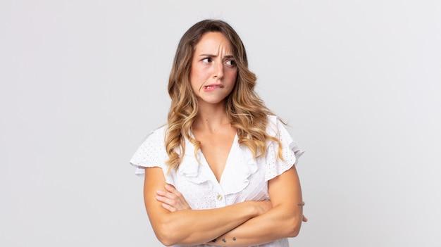 Dość szczupła kobieta wątpi lub myśli, przygryza wargę i czuje się niepewnie i zdenerwowana, chcąc skopiować przestrzeń z boku