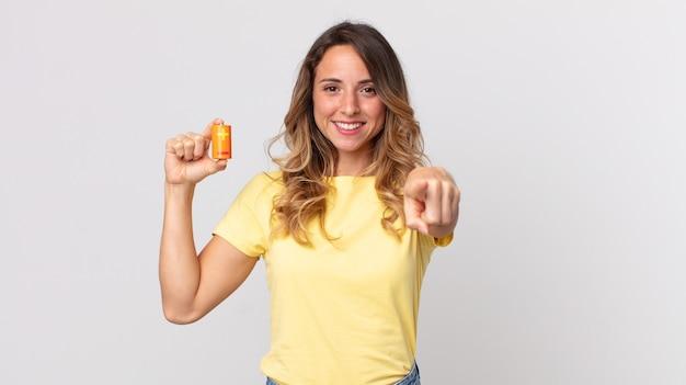 Dość szczupła kobieta wskazująca na kamerę, która cię wybiera i trzyma baterie