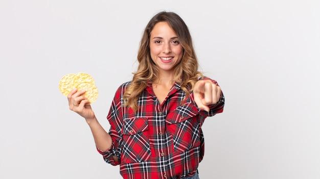 Dość szczupła kobieta wskazująca na kamerę, wybierająca cię i trzymająca dietetyczne ciastka ryżowe