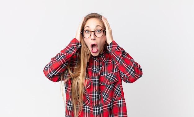 Dość szczupła kobieta wyglądająca na nieprzyjemnie zszokowaną, przestraszoną lub zaniepokojoną, z szeroko otwartymi ustami i zakrywającymi uszy dłońmi