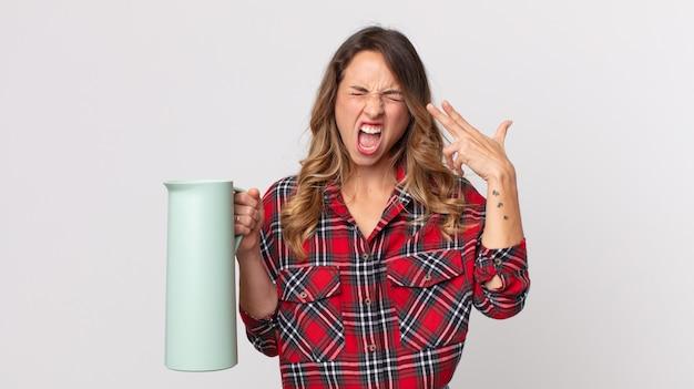 Dość szczupła kobieta wyglądająca na niezadowoloną i zestresowaną, samobójczy gest wykonujący znak pistoletu i trzymający termos z kawą