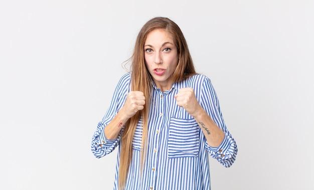 Dość szczupła kobieta wyglądająca na pewną siebie, złą, silną i agresywną, z pięściami gotowymi do walki w pozycji bokserskiej