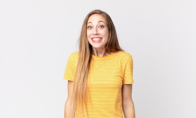 Dość szczupła kobieta wyglądająca na szczęśliwą i głupkowatą z szerokim, zabawnym, szalonym uśmiechem i szeroko otwartymi oczami