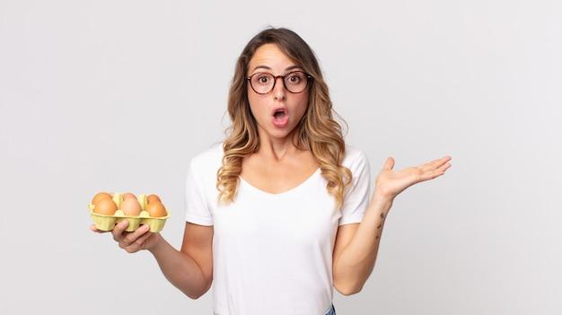 Dość szczupła kobieta wyglądająca na zaskoczoną i zszokowaną, z opuszczoną szczęką, trzymająca przedmiot i trzymającego pudełko z jajkami