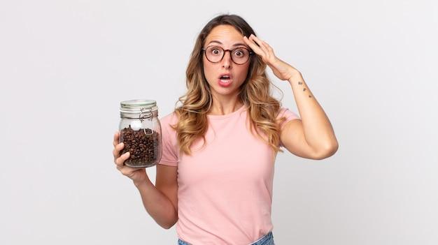 Dość szczupła kobieta wyglądająca na zaskoczoną, realizująca nową myśl, pomysł lub koncepcję i trzymająca butelkę ziaren kawy