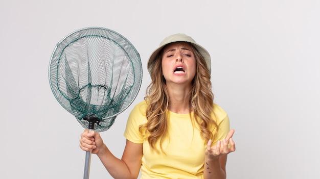 Dość szczupła kobieta wyglądająca na zdesperowaną, sfrustrowaną i zestresowaną, nosząca kapelusz i trzymająca siatkę na ryby