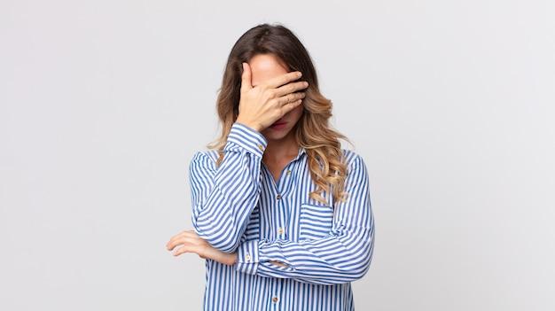 Dość szczupła kobieta wyglądająca na zestresowaną, zawstydzoną lub zdenerwowaną, z bólem głowy, zakrywająca twarz dłonią